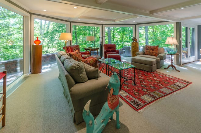 A wall of windows in the family room offers expansive views of the woods.
