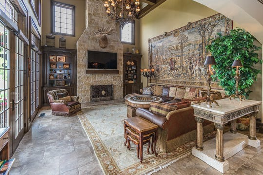 The homes rustic hearth room features a stone fireplace and French doors that open to the veranda. It also opens to the kitchen.