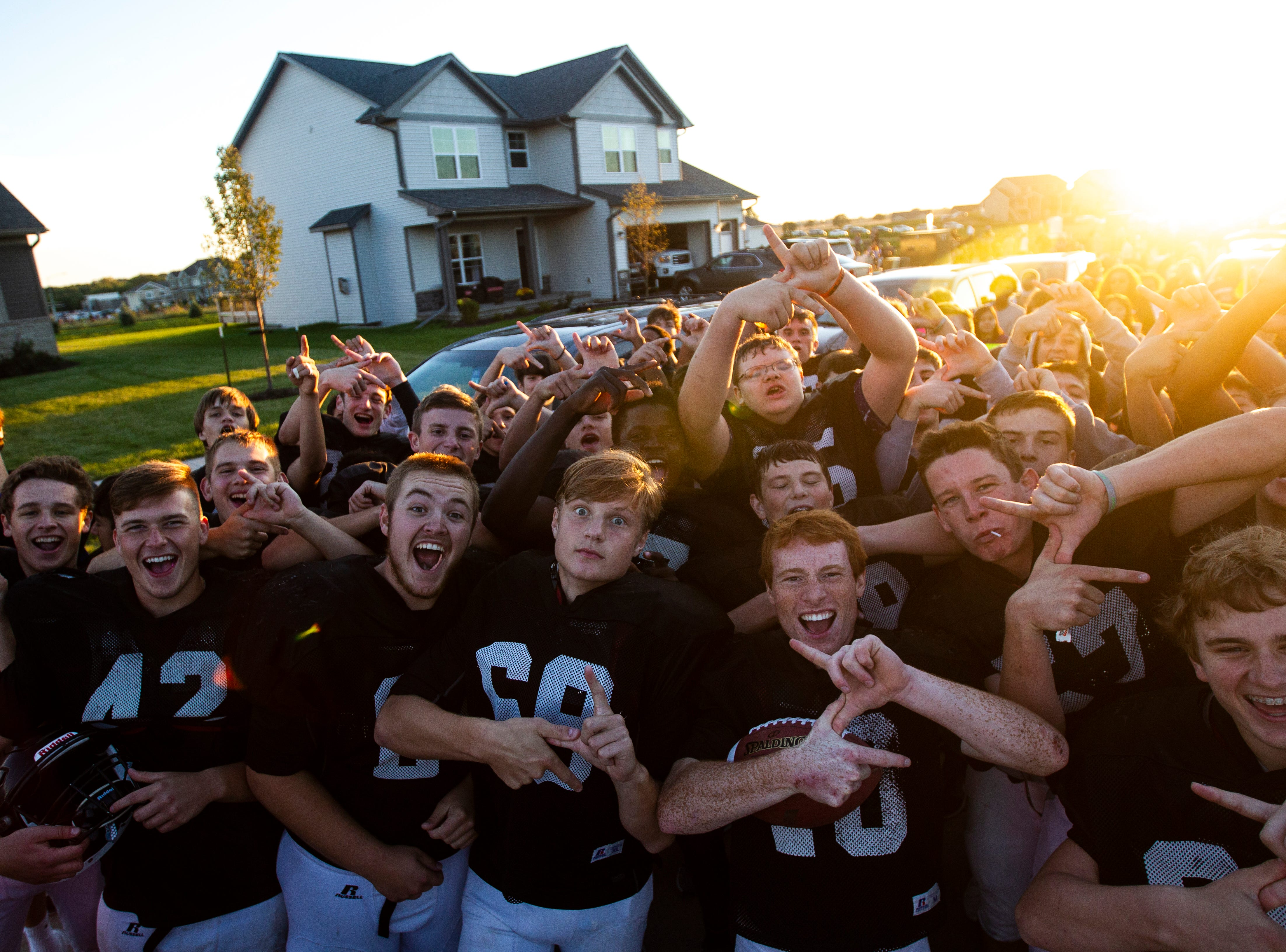 Members of the varsity football team pose during Liberty's homecoming parade on Wednesday, Sept. 26, 2018, in North Liberty, Iowa.