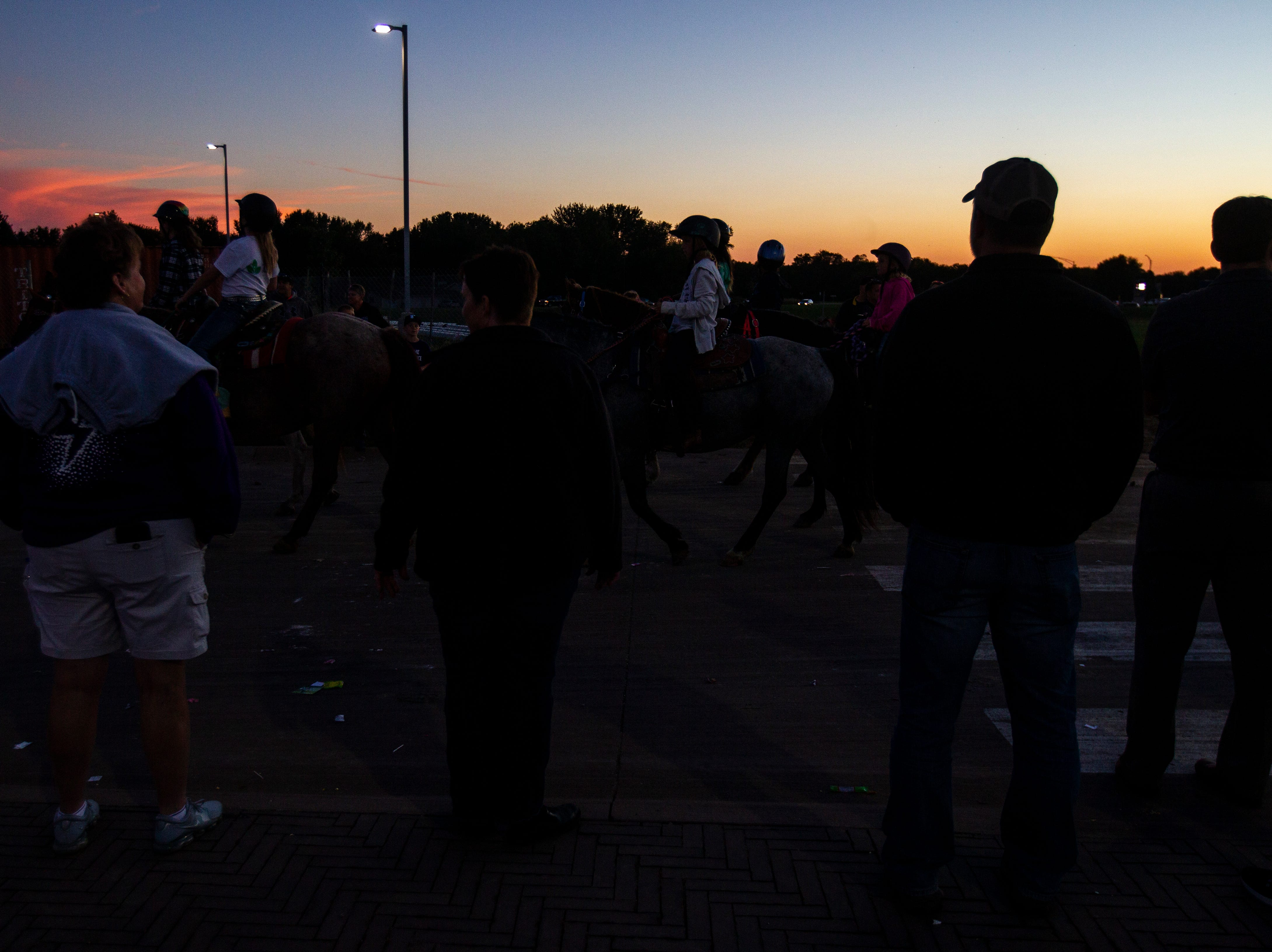 Student ride on a horses as the sun sets during Liberty's homecoming parade on Wednesday, Sept. 26, 2018, in North Liberty, Iowa.