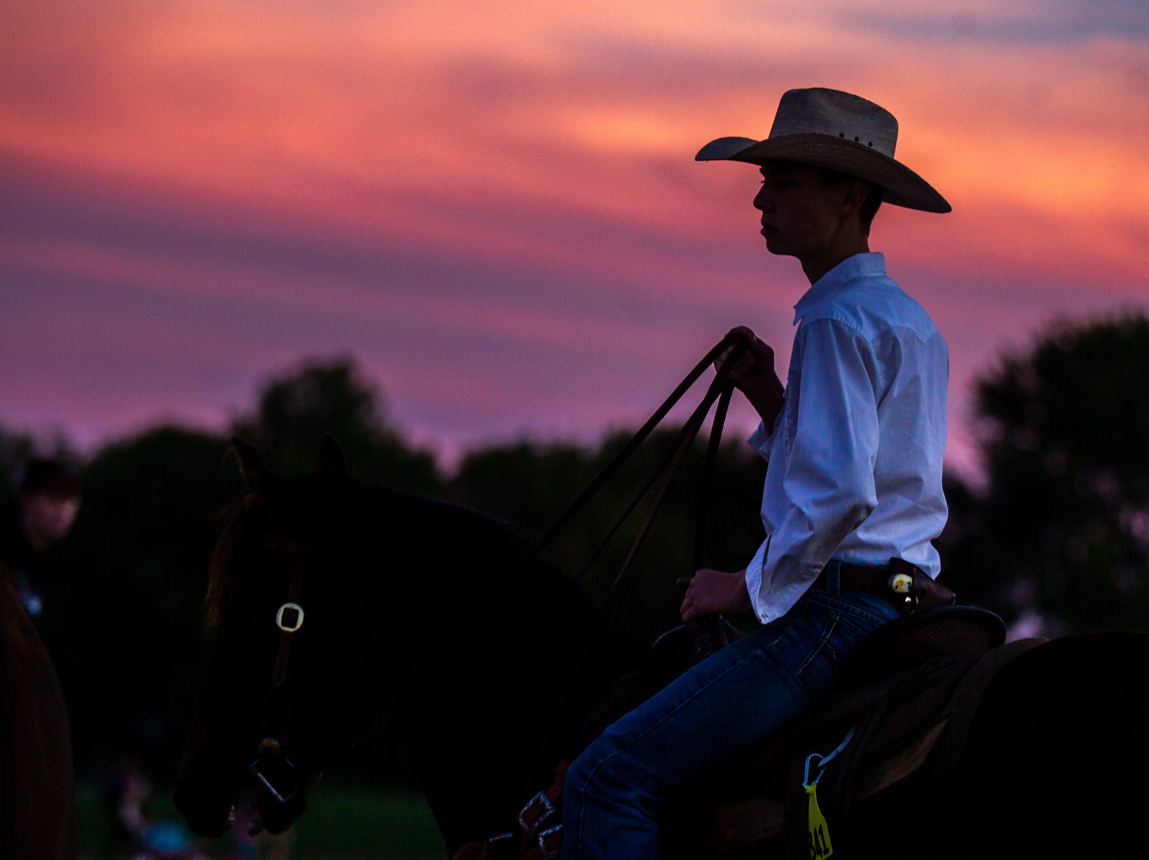 A student rides on a horse as the sun sets during Liberty's homecoming parade on Wednesday, Sept. 26, 2018, in North Liberty, Iowa.