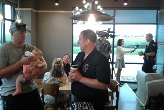 "National ""Coffee with a Cop"" day is Oct. 3 and will be held at three different McDonald's restaurants in this area.  This photo shows a joint event held at Dunn Brothers in Coralville Sept. 7 with Coralville police and fire department personnel.  Lt. Bill Erb of the fire service talks with Jacob Schutte and his baby daughter, May, while police officer Adam Jennings is interviewed by a TV reporter in the background."