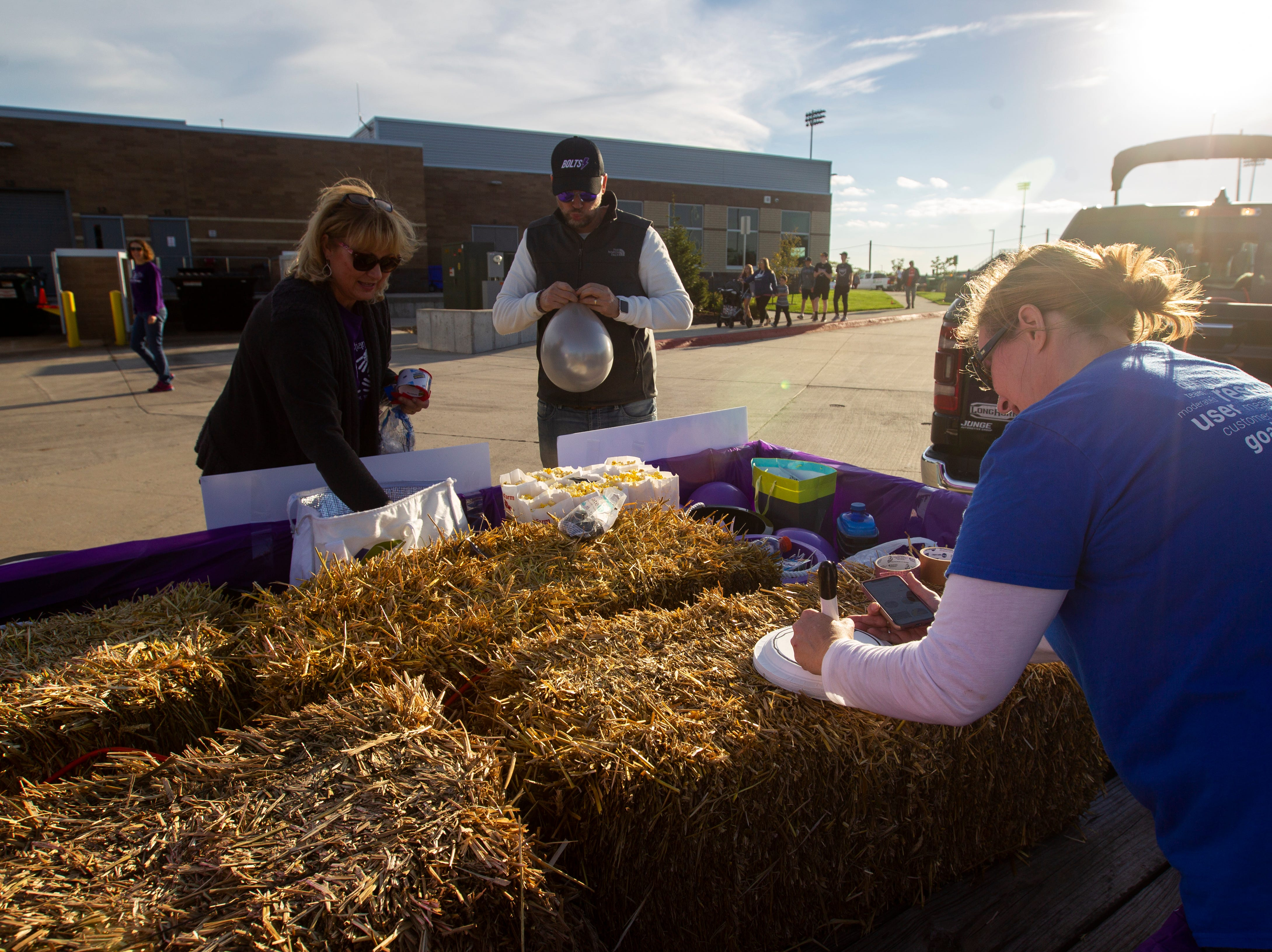 Liberty volleyball parents Lisa Potter (from left) Ryan Harvey, and Liz Harvey get ready during Liberty's homecoming parade on Wednesday, Sept. 26, 2018, in North Liberty, Iowa.