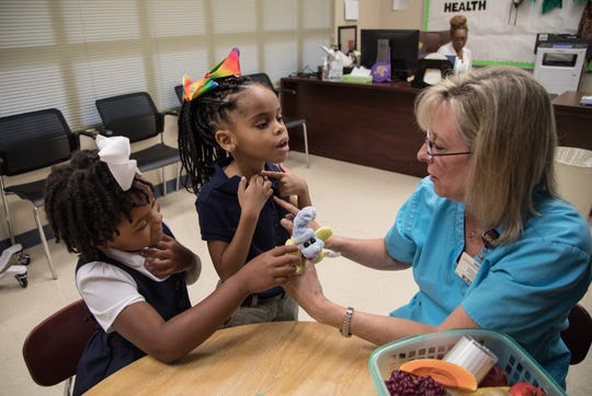Makynzee Taylor, left, and Raygen Pirtle, Galloway Elementary School students, show Anne Norwood, University of Mississippi Medical Center professor of nursing in the School of Nursing, how they breathe.