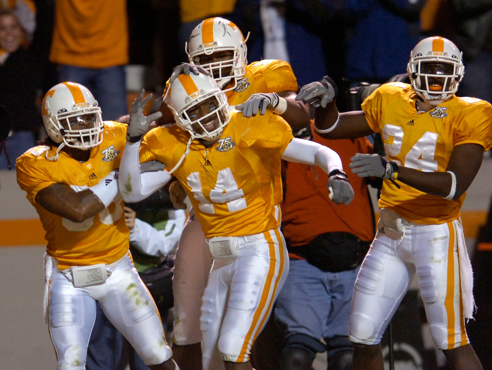 Tennessee defensive back Eric Berry (14) is congratulated by teammates after a 47-yard fumble return against South Carolina on Saturday at Neyland Stadium. The Vols survived a second half defensive collapse to win 27-24 in overtime, improving to 5-3 for the season.