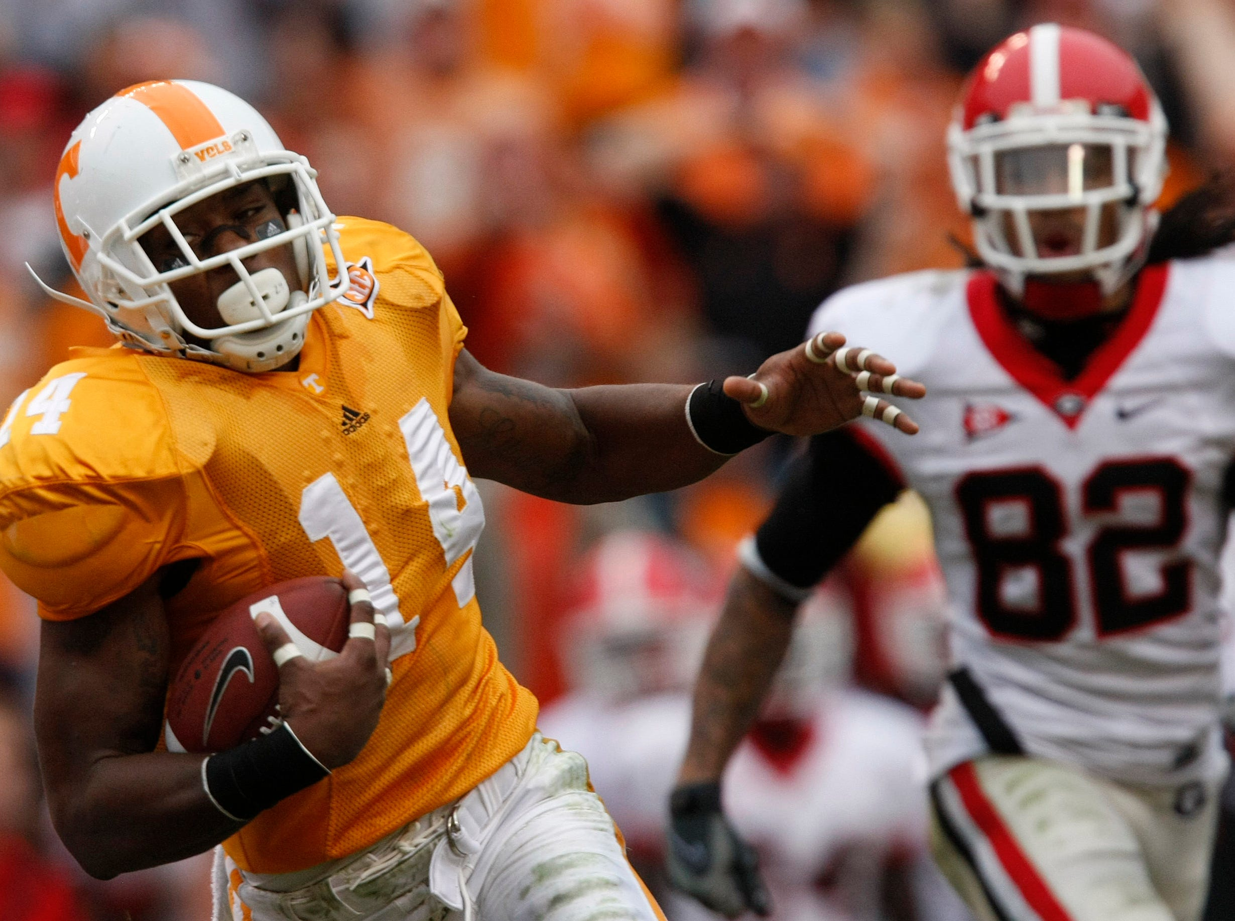 Tennessee's Eric Berry (14) returns an interception as he gets away from Georgia's Michael Moore (82) during the second half of an NCAA college football game Saturday, Oct. 10, 2009 in Knoxville, Tenn. Tennessee won 45-19.
