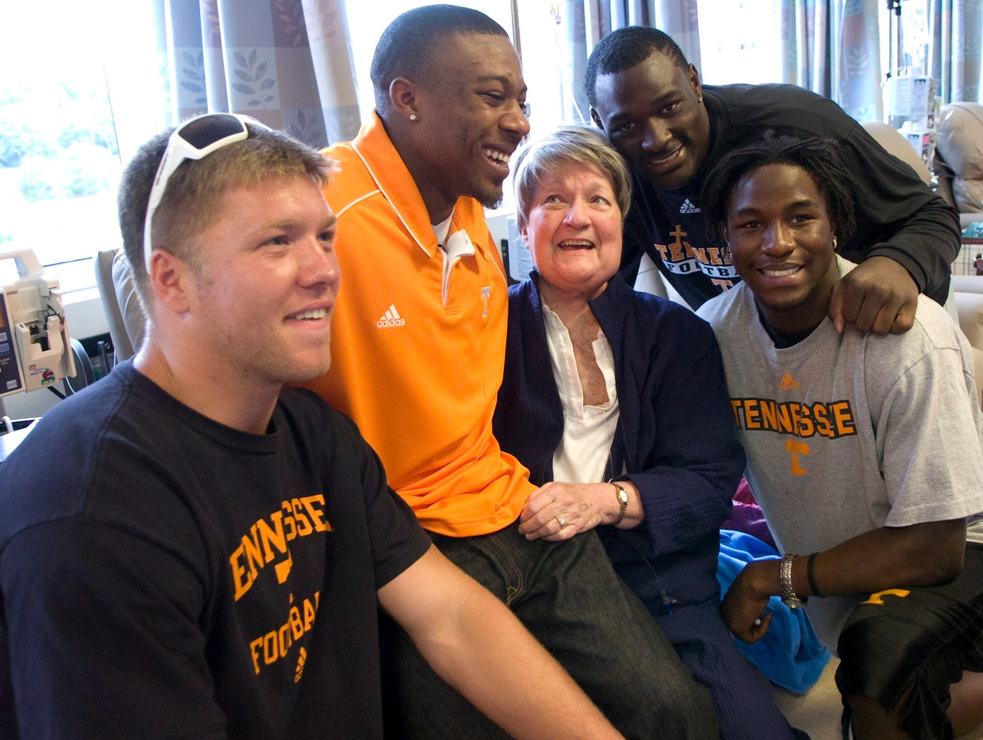 UT football players Chuck Karlosky, Eric Berry, Chris Walker and Denarius Moore, pose for a photo with cancer patient Ethel Campbell of Knoxville. The players visited patients at the UT Medical Center Cancer Institute on Wednesday.