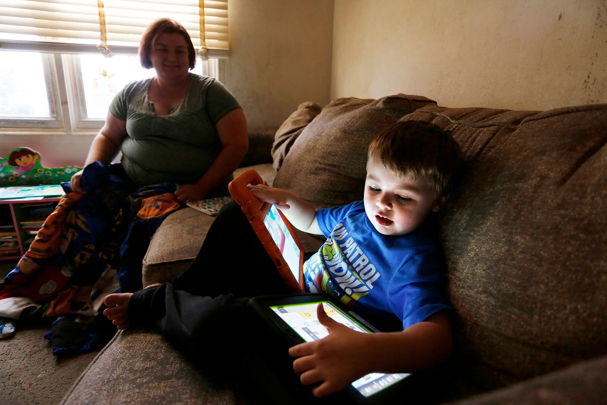Jacob Kendall, 4, plays with an iPad and a Tobii Dynavox as he shares the living room couch with his mother Tiffany Kendall Thursday, September 27, 2018, in their Lafayette home. Jacob, who is autistic, uses the iPad for entertainment and the Tobii Dynavox to communicate.