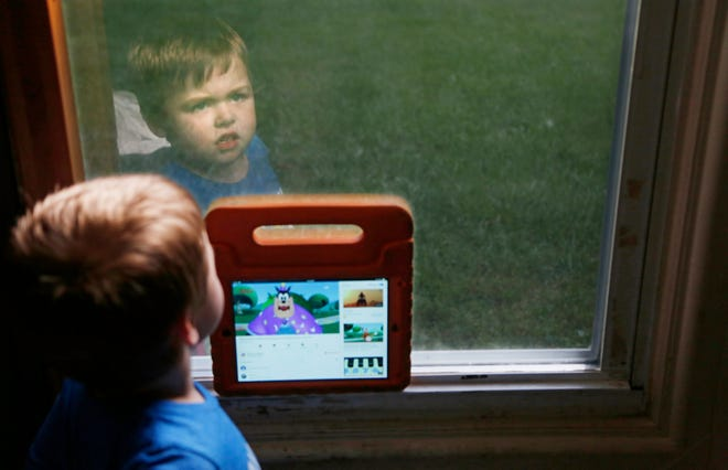 Jacob Kendall, 4, gazes out his bedroom window as he holds his iPad next to the glass Thursday in Lafayette. The iPad is a source of entertainment for Jacob, who is autistic.