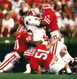 Ragin' Cajun defenders LaQuincy Phillips (93), Jonas Francois (90) and Ken Fogg (51) team up to stop Alabama fullback Martin Houston, who had six carries for 63 yards in the Crimson Tide's 25-6 win on Oct. 6, 1990, at Cajun Field.