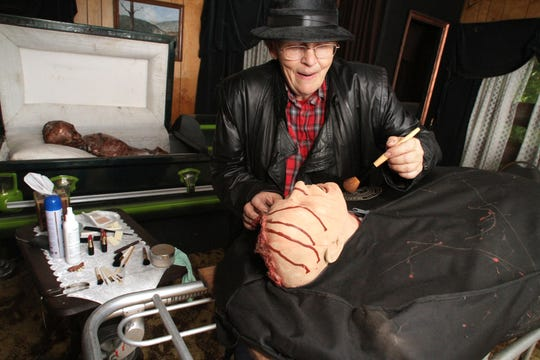 """Cindy Murphy-Broadbent, as an insane undertaker, prepares yet another """"victim"""" for interment at Terrorfied Forest and Manor near Pinckney, in 2013."""