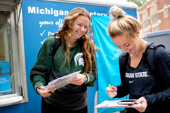 Michigan State University sophomores Taylor Myers, left, and Lindsay Hall register to vote at the Michigan Secretary of State mobile office outside the MSU Auditorium on Thursday, Sept. 25, 2018, in East Lansing.