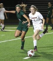 Madison's Chesney Davis vies for the ball with Lexington's Emma Sturts on Wednesday night.