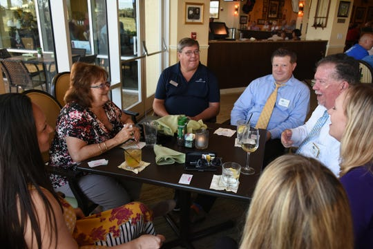 Tim Miller of Fuller Funeral Home, right, speaks to his group in a bonding exercise. The East Naples Merchants Association meets monthly, offering networkin and service opportunities.