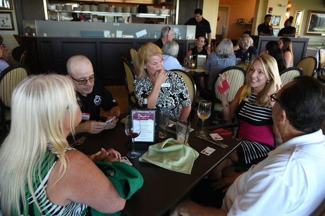Heidi Berge of WAVV101, right, speaks to her group in a bonding exercise. The East Naples Merchants Association meets monthly, offering networkin and service opportunities.