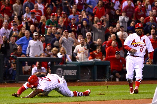 St. Louis Cardinals pinch runner Adolis Garcia (28) trips while running home attempting to score the tying run.