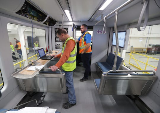 Scott Wedell (left), a traction service engineer with ABB Group, and Ryan Blazosk, a lead technician with Brookville Equipment Corp.'s streetcar division, work on testing the electrical power in a streetcar.