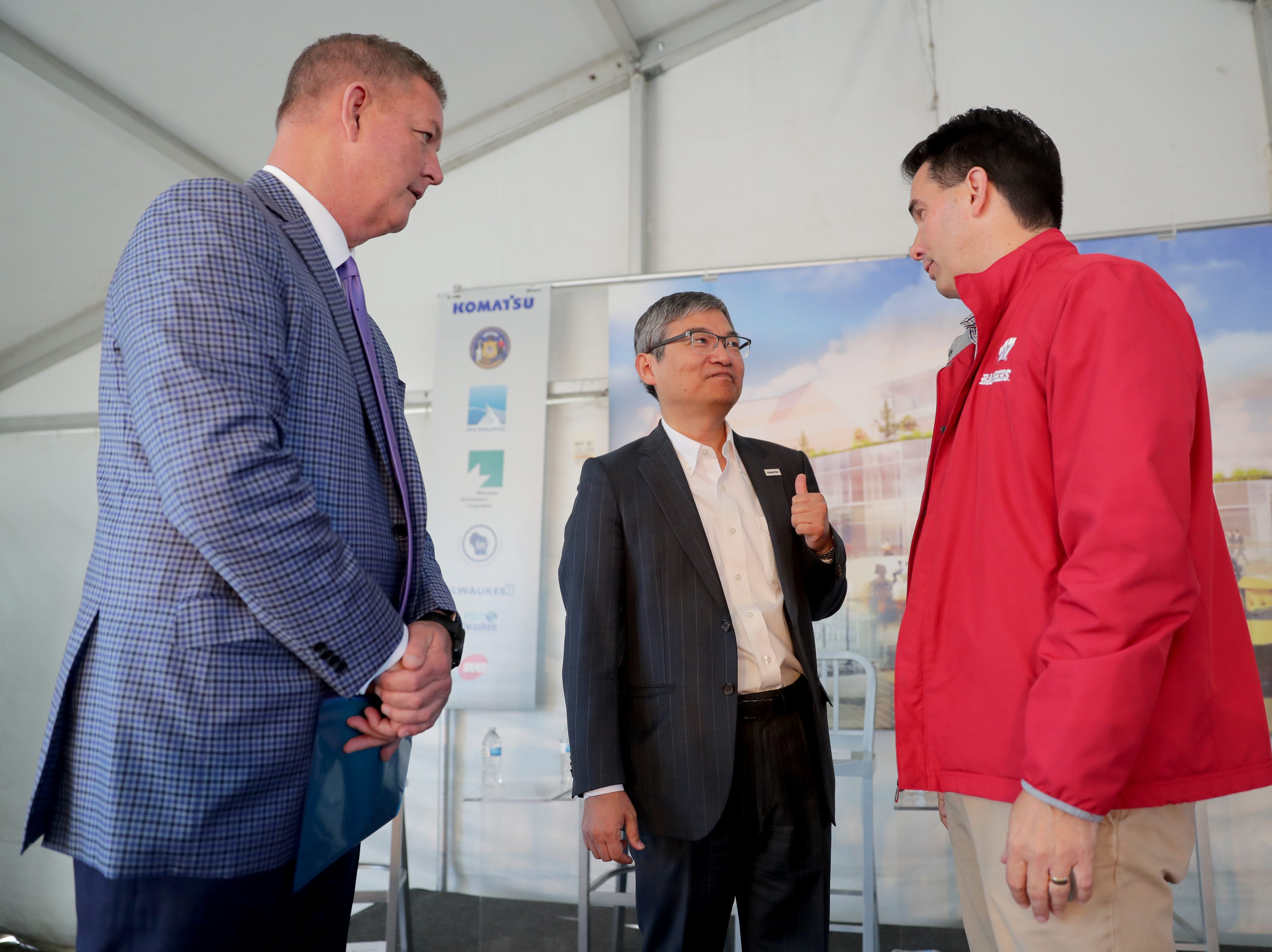 Ted Sasaki (center), CFO of Komatsu Mining Corp., talks with Gov. Scott Walker (right) and Tim Sheehy, president of the Metropolitan Milwaukee Association of Commerce, after the announcement.