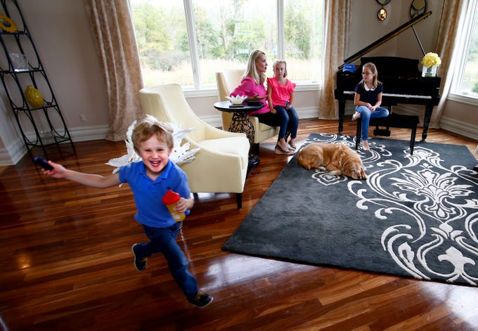 Carson Ford, 3, blurs through the living room while his mother Kathleen and sisters Kendal, 7, and Kayla, 9, talk. Carson and his family is living with care for his Type 1 Diabetes.