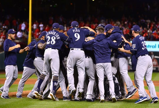 The Brewers celebrate on the infield Wednesday in St. Louis after clinching an NL playoff spot.