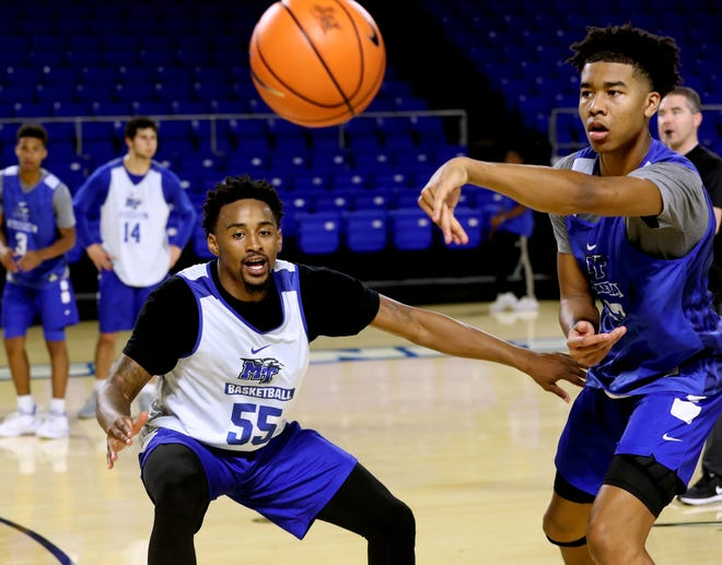 MTSU's Anthony Crump (13) passes the ball while Antonio Green (55) guards him during the team's first open practice Aug. 26.