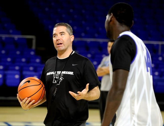 MTSU coach Nick McDevitt, left, works with his players during their first open practice Sept. 26 at Murphy Center.