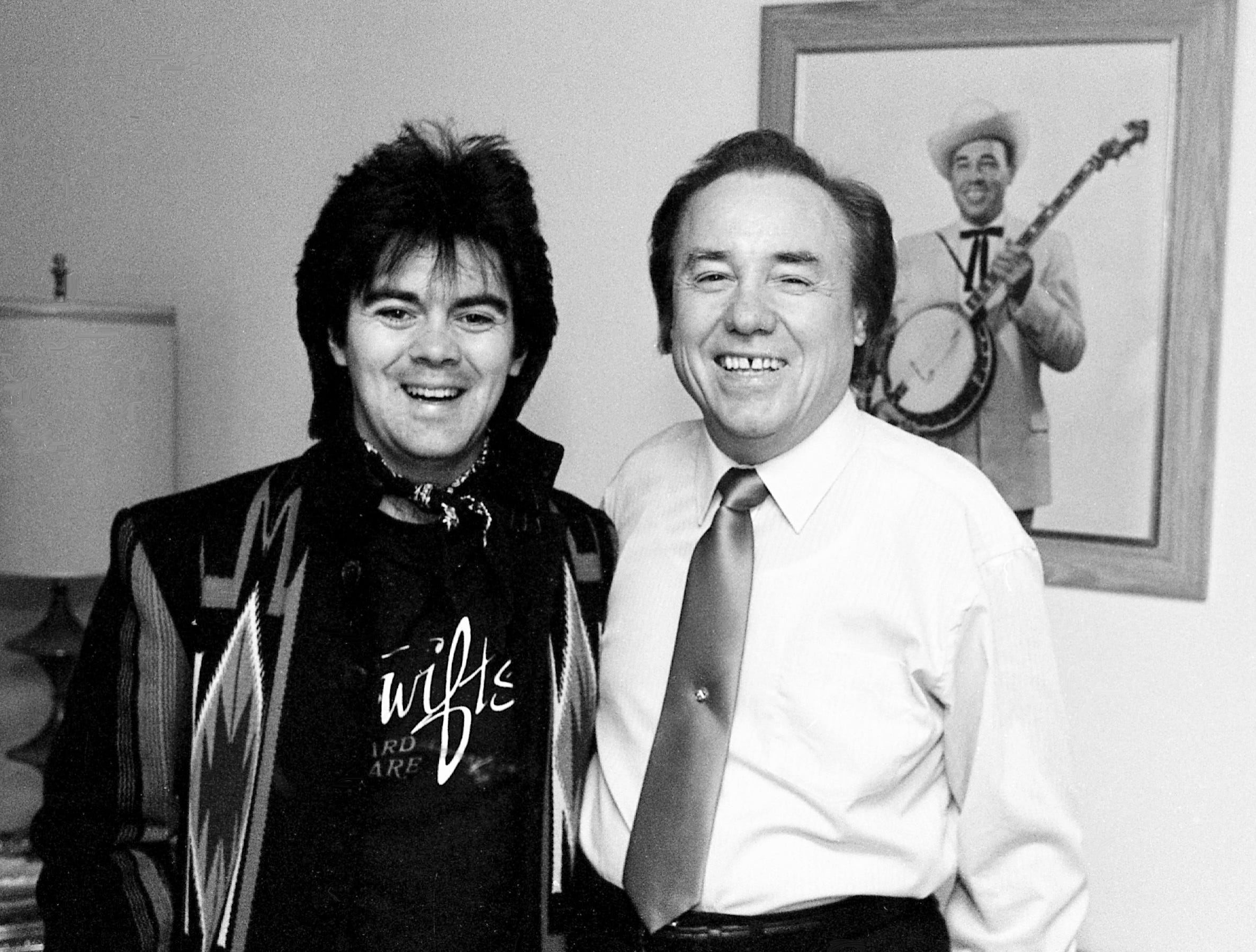 Close friend Marty Stuart, left, helps Earl Scruggs celebrate his 60th birthday Jan. 6, 1984.