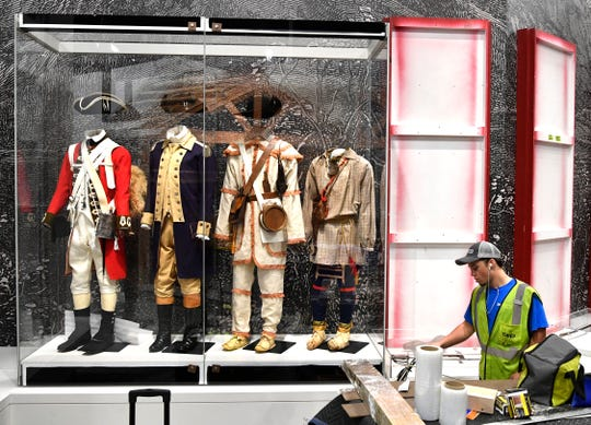 A worker vacuums around Revolutionary War military attire as displays are installed Thursday, Sept. 27, 2018, at the new Tennessee State Museum.
