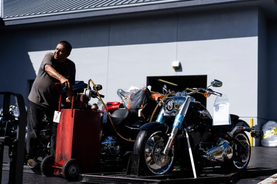 Leoonel Baca puts fuel in a newly purchased bike Thursday morning at the Naples Harley Davidson garage. Baca has worked in the Detail Service Department for 10 years. He said that after Saturday, Sept. 29, 2018, when the shop closes, he will not be working with motorcycles anymore.