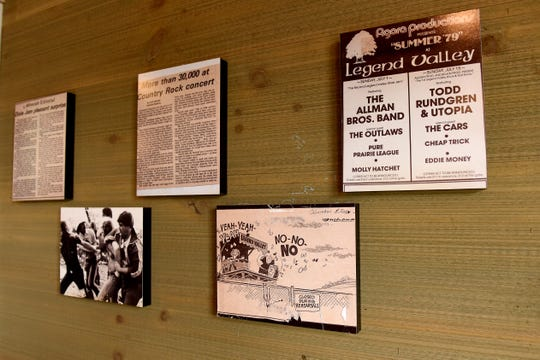 Framed playbills and articles about Legend Valley in Thornville, including an editorial cartoon about a judge who wanted to close the venue.