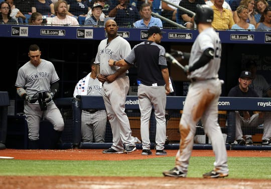 Sep 27, 2018; St. Petersburg, FL, USA; New York Yankees manager Aaron Boone (17) holds back starting pitcher CC Sabathia (52) as catcher Austin Romine (28) gets thrown a wild pitch behind him during the sixth inning by Tampa Bay Rays relief pitcher Andrew Kittredge (36) (not pictured)  at Tropicana Field.