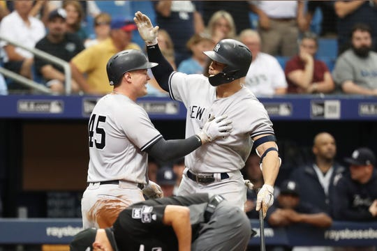 New York Yankees first baseman Luke Voit (45) is congratulated by left fielder Giancarlo Stanton (27) as he hits a home run during the sixth inning against the Tampa Bay Rays at Tropicana Field.