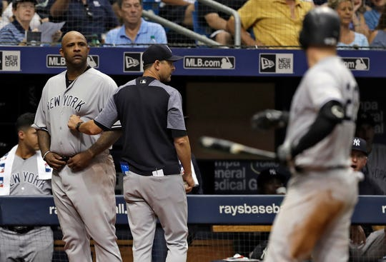 New York Yankees manager Aaron Boone, center, restrains starting pitcher CC Sabathia, left, after Tampa Bay Rays pitcher Andrew Kittredge threw behind Yankees batter Austin Romine, right, during the sixth inning of a baseball game Thursday, Sept. 27, 2018, in St. Petersburg, Fla.