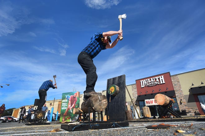 Lumberjacks Nick Hastedt (foreground) and Dave Weatherhead (rear) of Timberworks Jackshow.com from Wisconsin, compete in the wood chopping contest during the opening day for Duluth Trading Company in Ramsey on 09/27/18.