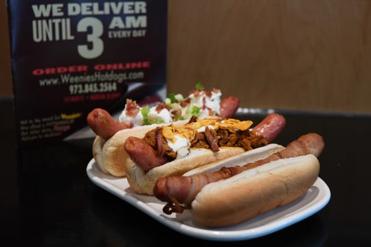 (From left) Creamy Pig, a hotdog with cream cheese, bacon and scallions; Hey Dude, a hotdog with pulled pork, ranch, and Doritos; and a bacon wrapped hotdog at Weenies in Madison on Wednesday, September 26, 2018.