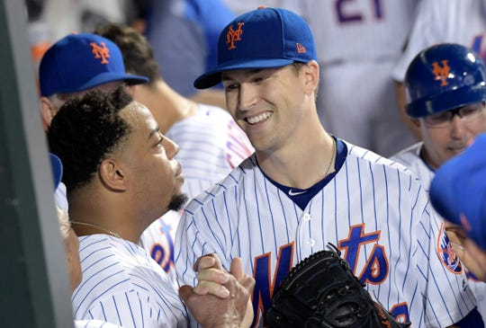 New York Mets pitcher Jacob deGrom, right, celebrates with Dominic Smith after deGrom left the baseball game in the eighth inning Wednesday, Sept. 26, 2018, in New York. The Mets defeated the Atlanta Braves 3-0. (AP Photo/Bill Kostroun)