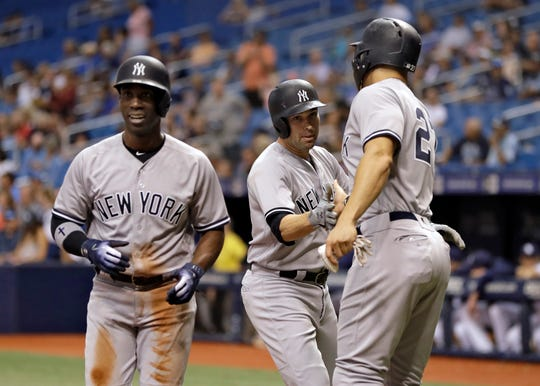 New York Yankees' Neil Walker, center, celebrates with Andrew McCutchen, left, and Giancarlo Stanton after Walker hit a three-run home run off Tampa Bay Rays relief pitcher Ryne Stanek during the first inning of a baseball game Wednesday, Sept. 26, 2018, in St. Petersburg, Fla.