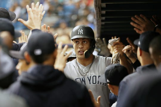 Sep 26, 2018; St. Petersburg, FL, USA; New York Yankees right fielder Giancarlo Stanton (27) is congratulated after scoring a run against the Tampa Bay Rays during the first inning at Tropicana Field.