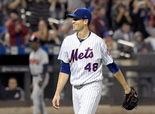 New York Mets pitcher Jacob deGrom smiles as he walks off the field after the eighth inning of a baseball game against the Atlanta Braves Wednesday, Sept. 26, 2018, in New York. The Mets defeated the Braves 3-0. (AP Photo/Bill Kostroun)