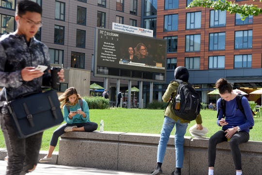 """Christine Blasey Ford gives testimony before the Senate Judiciary Committee about her sexual accusations that Judge Brett M. Kavanaugh sexually assaulted her when Ford was fifteen years old. The hearing was shown on a large screen in """"The Yard"""" on College Ave. on Rutgers University in front of the Sojourner Truth Apartments Thursday, September 27, 2018."""