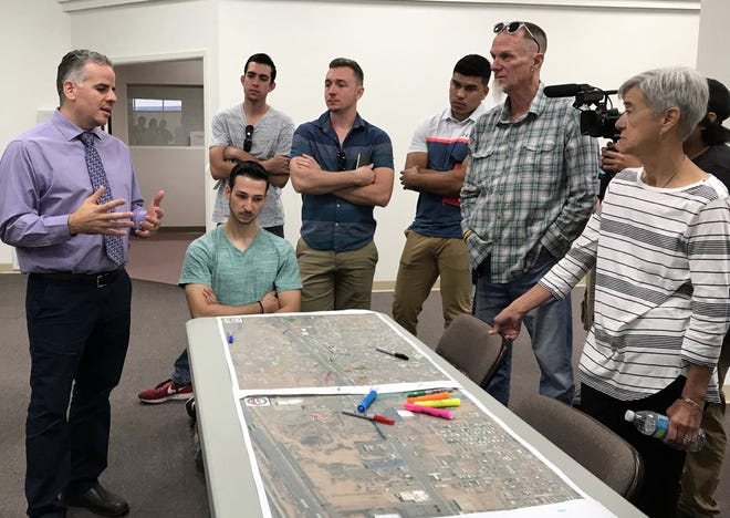 City Councilor Dr. Victor Cruz, at left, is shown discussing the ongoing incubator and revitalization project with students and staff from the University of New Mexico and Woodbury University/San Diego.