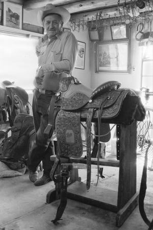 Slim Green poses in his saddle shop in Tesuque, N.M.