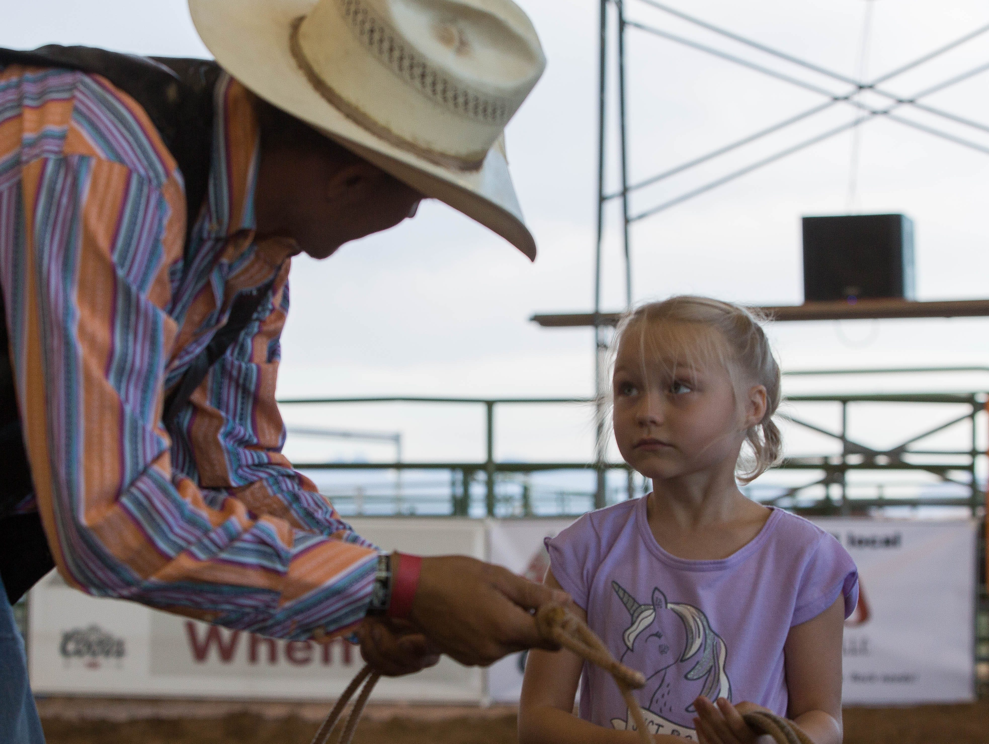 Zoey Froberg, 6, gets a few tips for throwing a lasso from Blaine Pinochi, a member of the New Mexico State Univeristy rodeo team, in the Kids and Fan Zone of the Southern New Mexico State Fair and Rodeo, Wednesday, Sept. 26, 2018.