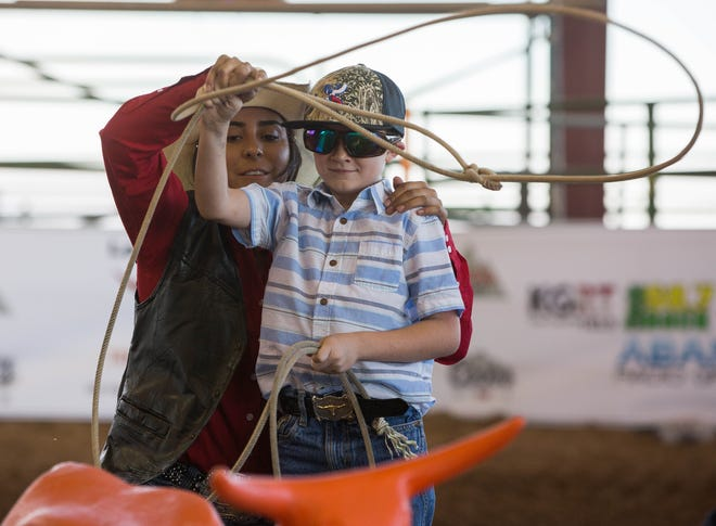 Keylie Kemple, a member of the New Mexico State University Rodeo team, teaches Ethan Myers, 7, how to rope a steer, Wednesday, Sept. 26, 2018 in the Kids and Fan Zone at the Southern New Meico State Fair and Rodeo, before the start of the Rumble on the Rio bull riding competition.