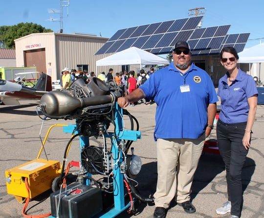 Dave Ortiz, left and Amy Ballard, right, of CNM stand next to an Allison 250 Turboshaft Engine at the 2018 NMAAA STEM Expo at Alamogordo White Sands Regional Airport Thursday.