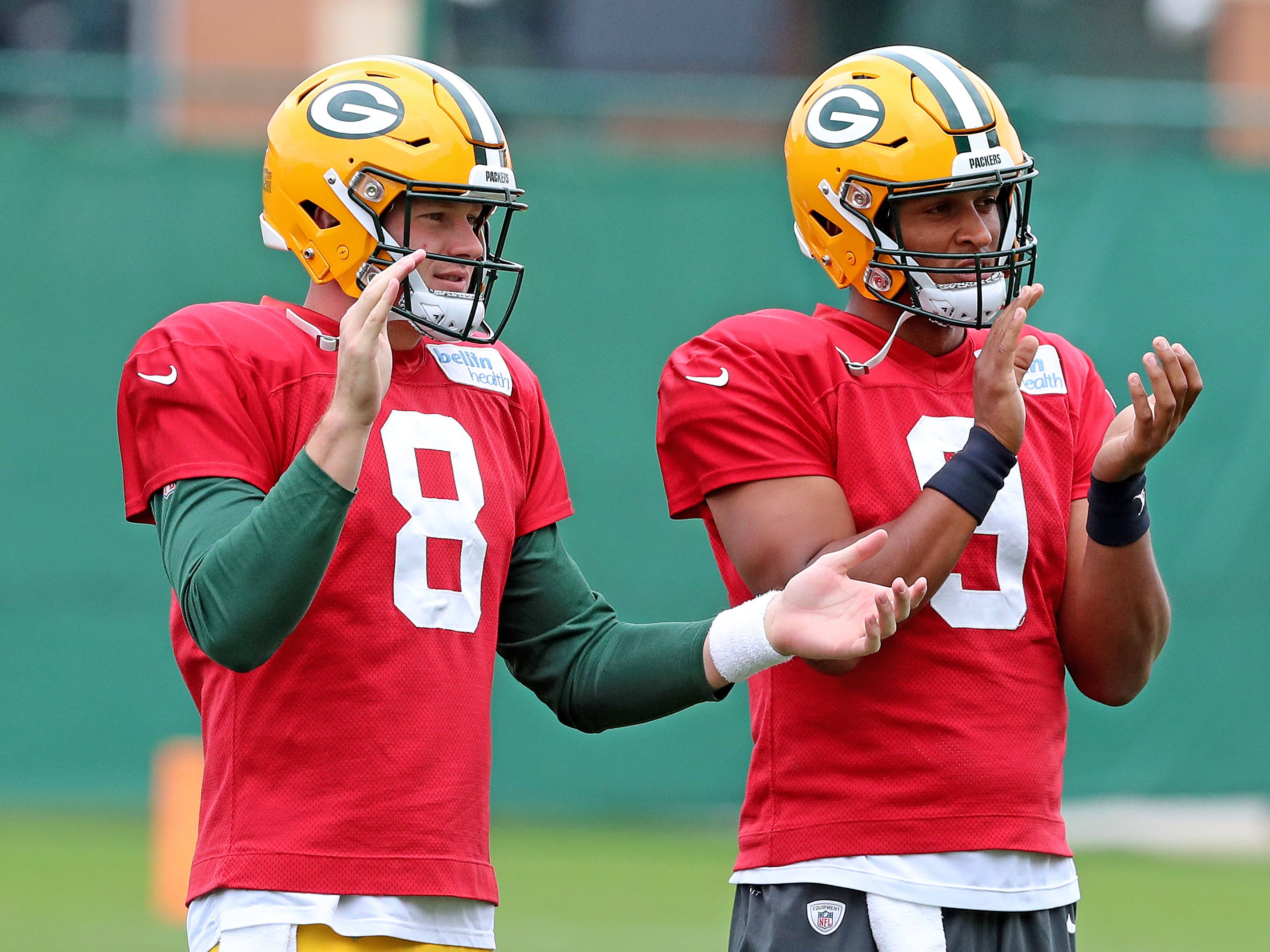 Green Bay Packers quarterback Tim Boyle (8) and quarterback DeShone Kizer (9) applaud as quarterback Aaron Rodgers (12) returns to practice on Clarke Hinkle Field Thursday, September 27, 2018 in Ashwaubenon, Wis