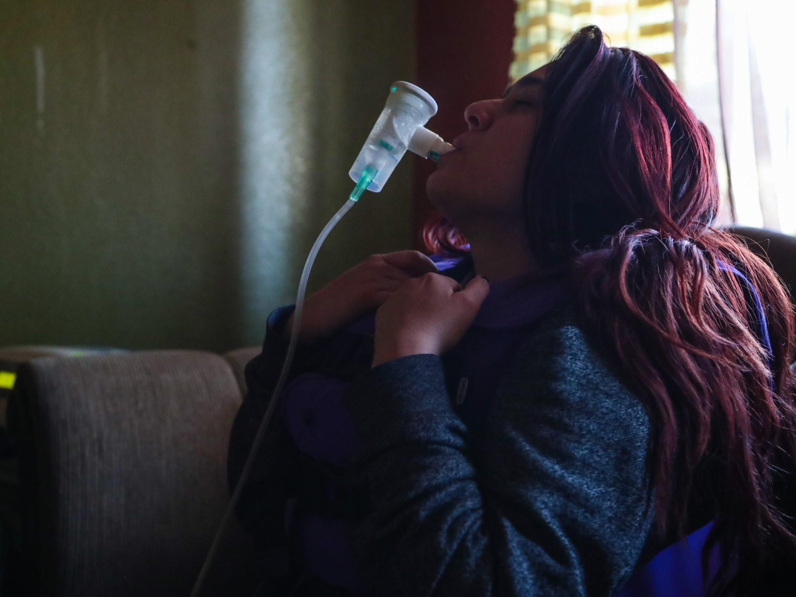 Michelle Dugan-Delgado uses a neublizer treatment and a vest airway-clearing system twice a day to improve her lung functioning and prevent asthma attacks.