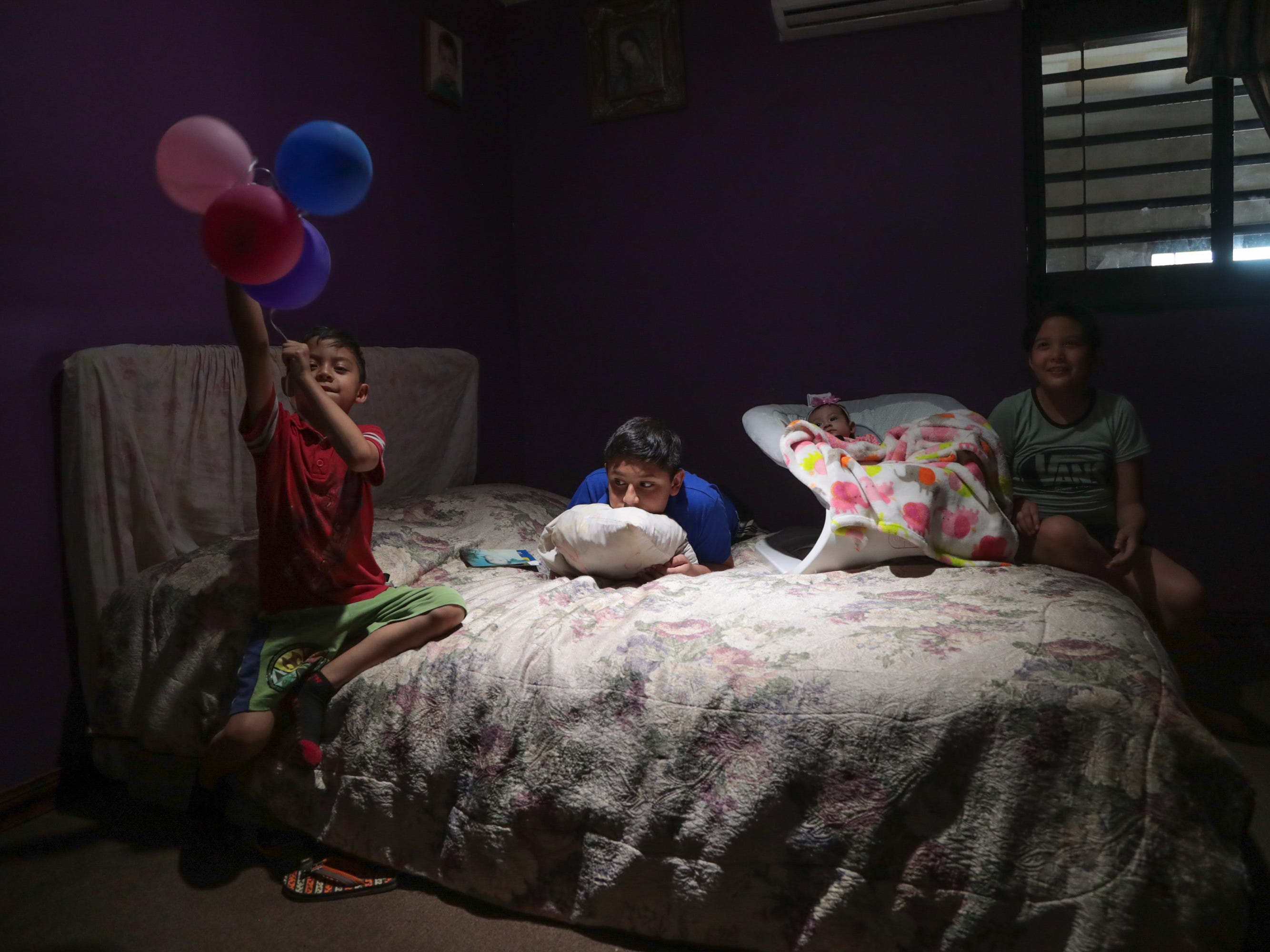 Luis Raudel Arámbula watches TV in his room with his cousins in Mexicali on May 8, 2018. He has asthma and often stays inside to avoid the bad air outside.