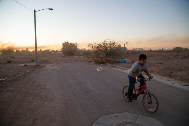 A boy rides his bike on the edge of his neighborhood in Mexicali. Behind him, on the other side of the vacant lot, is the Industrias Zahori factory.