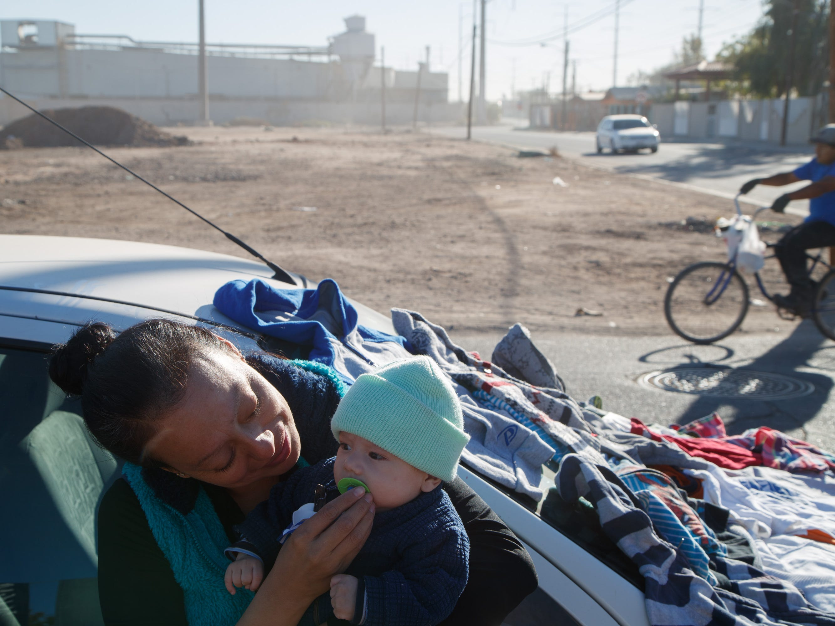 Yaneth Pérez comforts her 3-month-old son, Israel, while selling used clothing in Mexicali on Dec. 12, 2017.